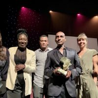 Sulaiman Addonia accepts his Golden Afro Artistic Award, flanked onstage by friends. Source: Sulaiman Addonia's Twitter.
